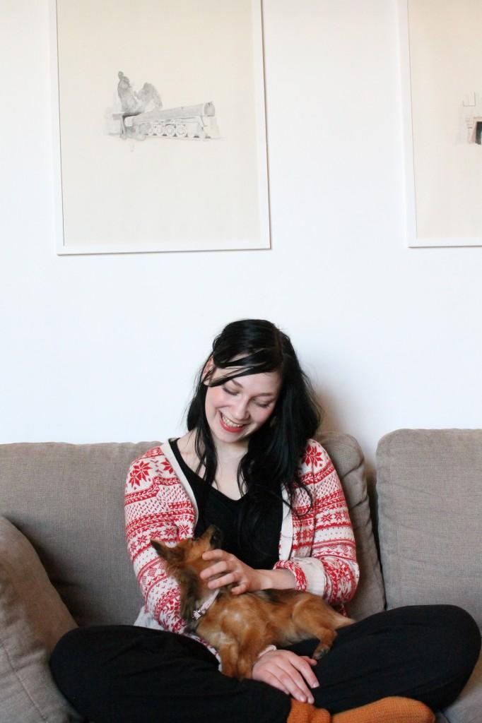 Betty hjemme i sofaen sin, sammen med en hund hun passer i noen dager